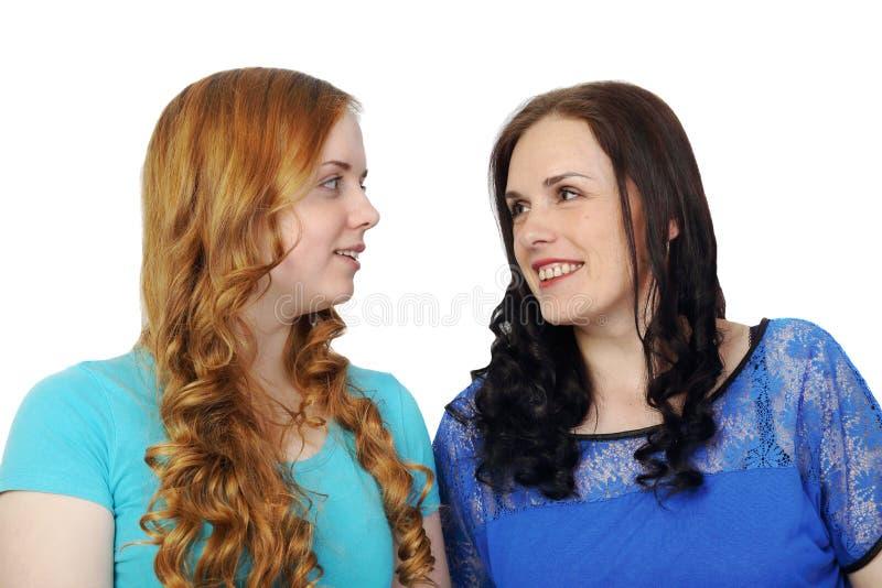 Roodharige jong meisje en volwassen donkerbruine vrouw stock foto