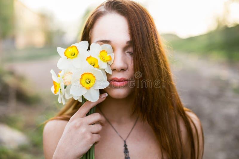 Roodharige jonge dame met boeket van gele narcissen stock afbeelding