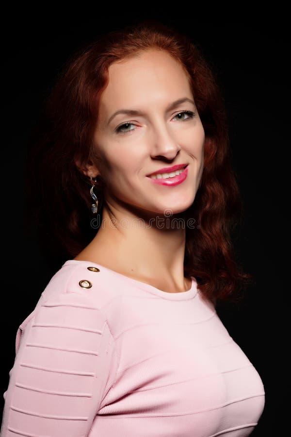 Roodharige jonge vrouw in de studio op een zwarte achtergrond royalty-vrije stock fotografie
