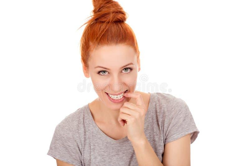 Roodharige nieuwsgierige vrouw het bijten vingerspijkers die u bekijken camera stock foto's
