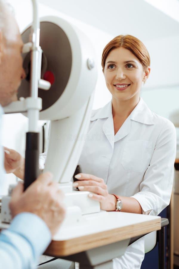 Roodharige richtende oftalmoloog die goed terwijl het werken voelen stock afbeeldingen