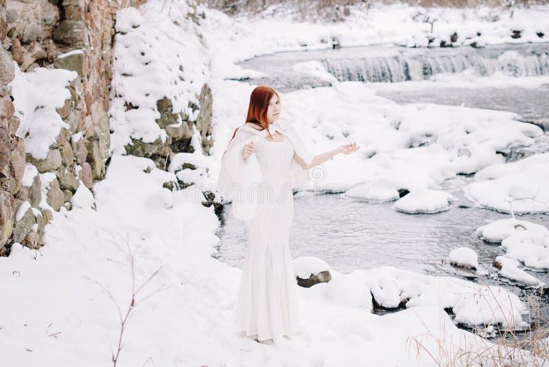 Roodharige schoonheid op de snow-covered bank van de rivier stock afbeeldingen