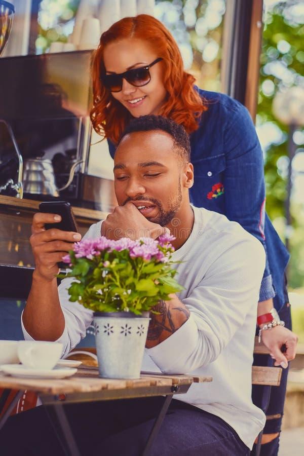 Roodharige vrouwelijke en Zwarte glimlachen mannelijke het gebruiken smartphone royalty-vrije stock foto