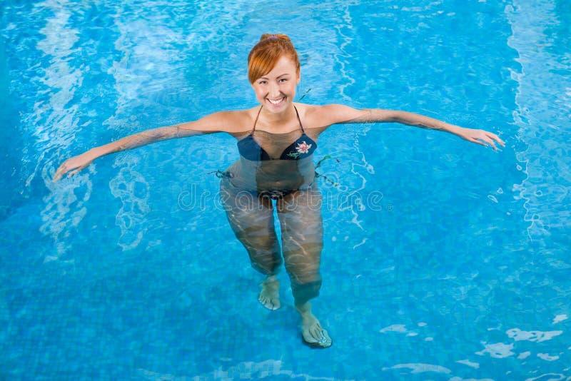 Roodharige in zwembad stock fotografie