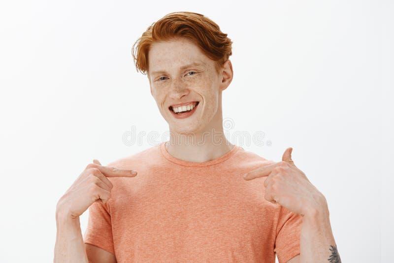 Roodharigekerel die over zijn laatste doel tijdens gelijke opscheppen, die trots van zich, richtend op borst met wijsvingers zijn stock afbeeldingen