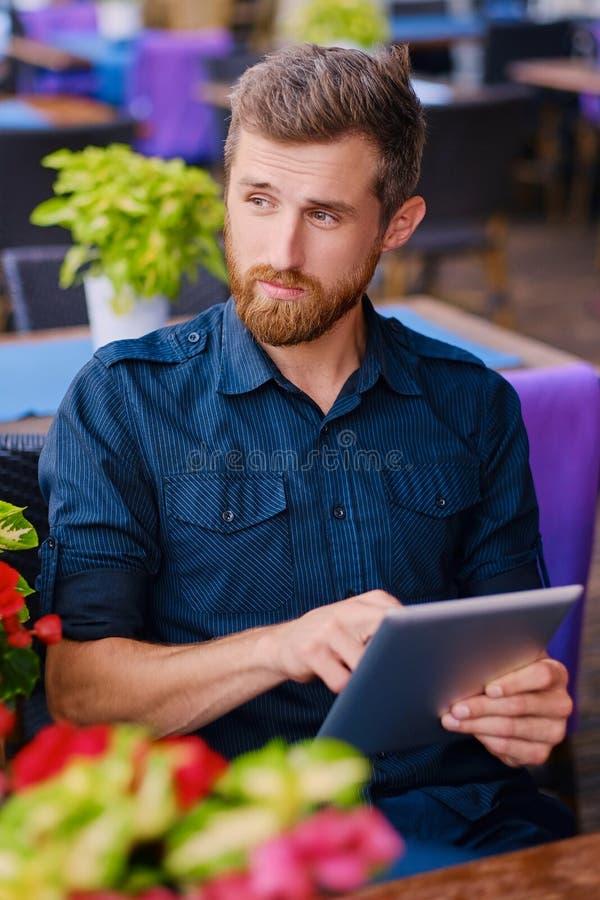 Roodharigemannetje die een tabletpc met behulp van bij de lijst stock fotografie