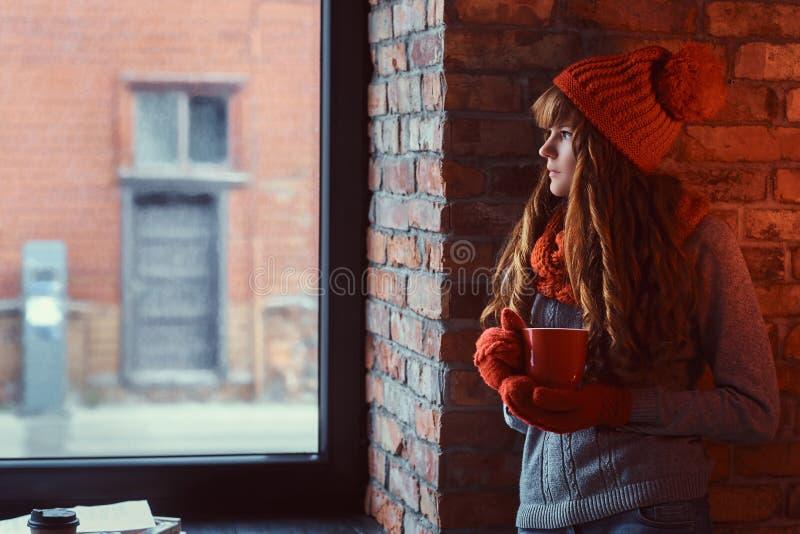 Roodharigemeisje die een warme sweater en een hoed dragen die een kop van koffie houden terwijl het leunen op een bakstenen muur  stock foto