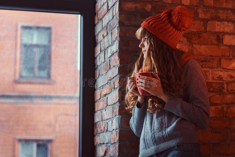 Roodharigemeisje die een warme sweater en een hoed dragen die een kop van koffie houden terwijl het leunen op een bakstenen muur  royalty-vrije stock afbeeldingen