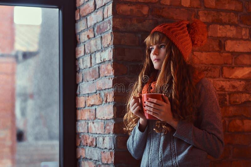 Roodharigemeisje die een warme sweater en een hoed dragen die een kop van koffie houden terwijl het leunen op een bakstenen muur  stock afbeeldingen