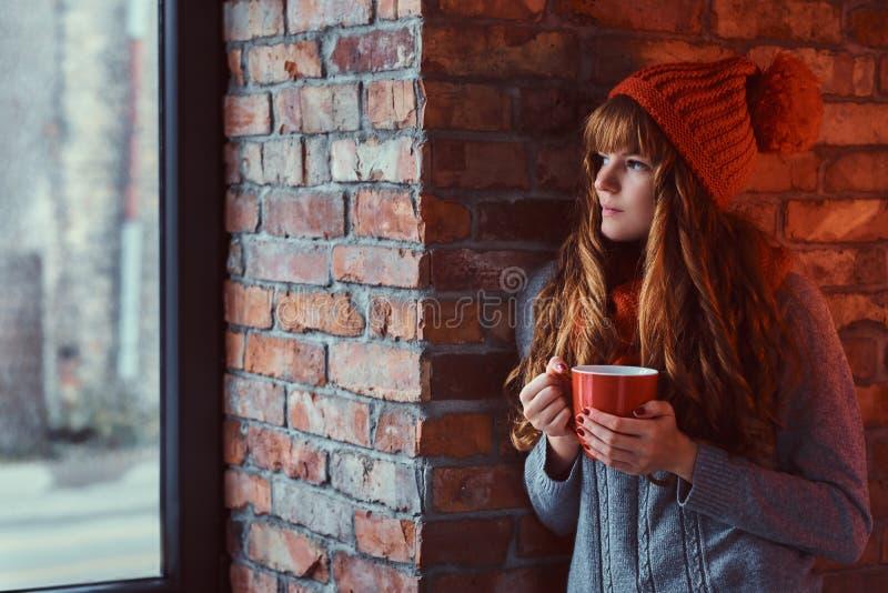 Roodharigemeisje die een warme sweater en een hoed dragen die een kop van koffie houden terwijl het leunen op een bakstenen muur  royalty-vrije stock afbeelding