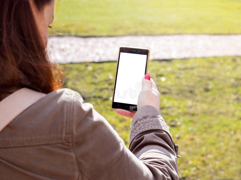 Roodharigemeisje die smartphone in openlucht gebruiken Het witte scherm De de lentetijd? nam bladeren, natuurlijke achtergrond to royalty-vrije stock foto's