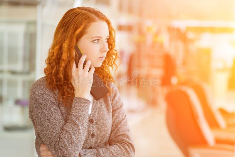 Roodharigemeisje die telefonisch spreken. stock foto