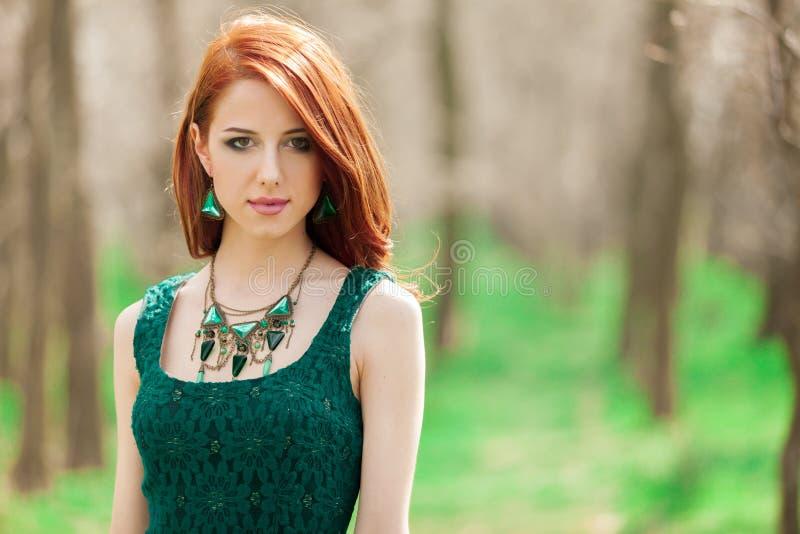 Roodharigemeisje in groene kleding in het park royalty-vrije stock afbeelding