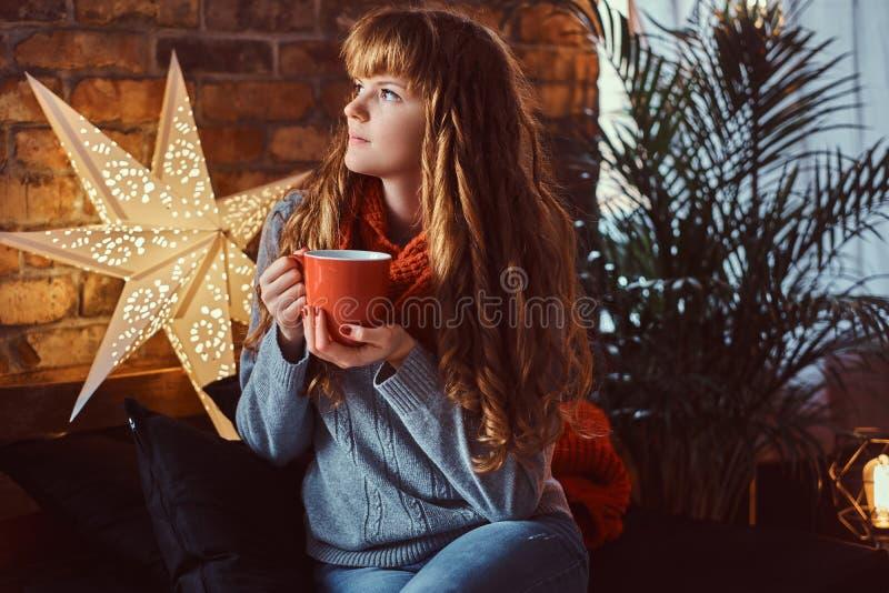 Roodharigemeisje het verwarmen met een kop van koffie in een verfraaide woonkamer in Kerstmistijd stock fotografie
