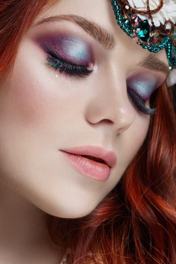 Roodharigemeisje met heldere make-up en grote zwepen Geheimzinnige feevrouw met rood haar De grote ogen en de gekleurde schaduwen royalty-vrije stock afbeelding