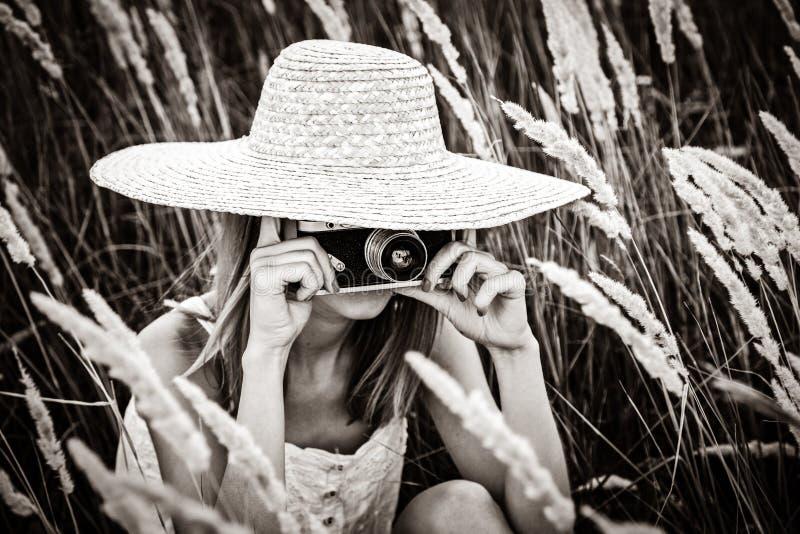 Roodharigemeisje met oude camera stock fotografie