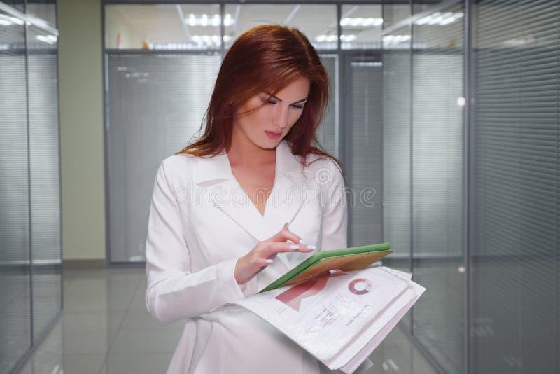 Roodharigeonderneemster in kostuum met tablet en document die zich in gang van bureau bevinden royalty-vrije stock foto