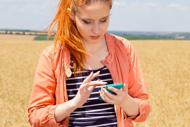 Roodharigevrouw die een bericht verzenden die dekking op mobiele telefoon zoeken stock fotografie