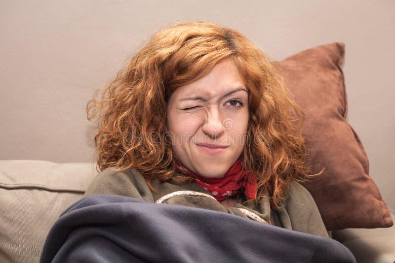 Roodharigevrouw met één oog het gesloten ontspannen op bank royalty-vrije stock afbeelding