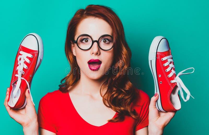 Roodharigevrouw met rode gumshoes stock afbeelding