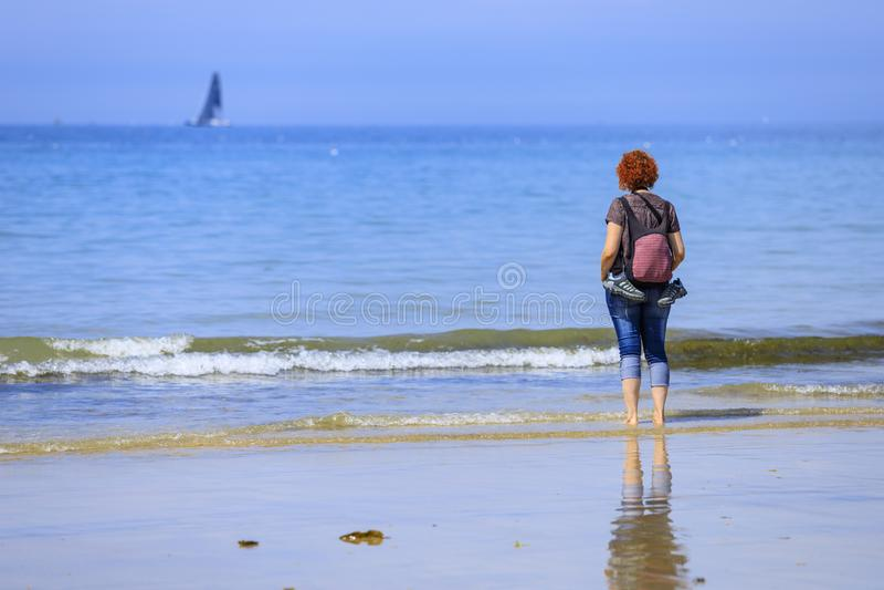 Roodharigevrouw op de kust stock foto's