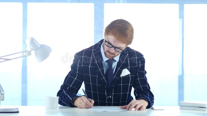 Roodharigezakenman Paperwork die, die en aan Laptop schrijven werken royalty-vrije stock afbeeldingen