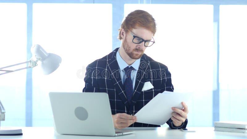 Roodharigezakenman Reading Documents in Bureau, Studie stock fotografie