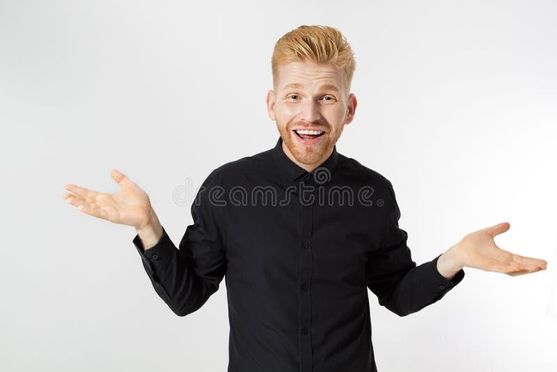 Roodkopman weet het niet of weet het niet zeker Skeptisch, onzeker, onzeker, twijfelachtig concept Jonge blanke man in zwarte kle stock foto's