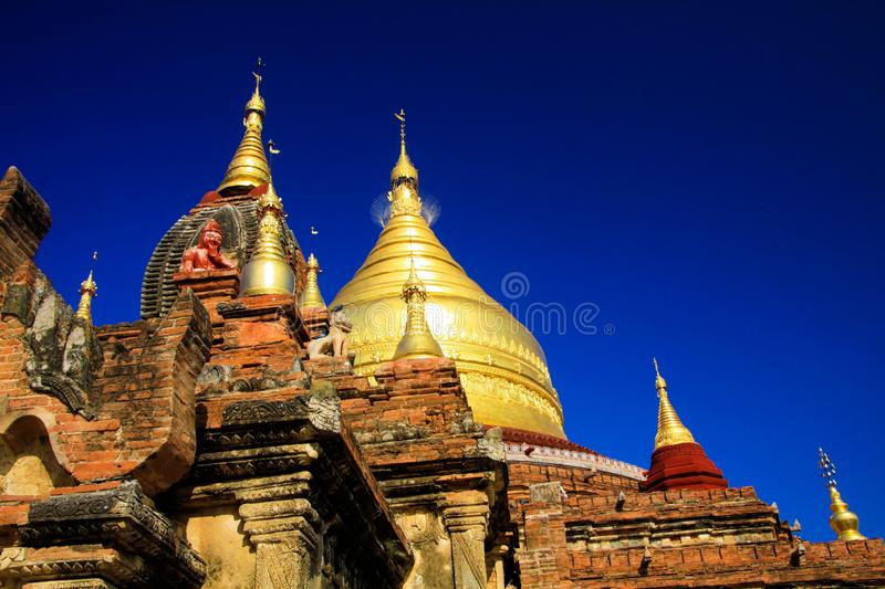 Roof of ancient brick stone temple with golden dome contrasting with deep blue sky -  Bagan, Myanmar. Roof of ancient brick stone temple with golden dome stock photo