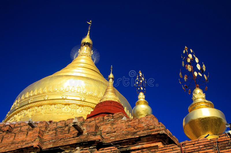 Roof of ancient brick stone temple with golden dome contrasting with deep blue sky -  Bagan, Myanmar. Roof of ancient brick stone temple with golden dome royalty free stock image