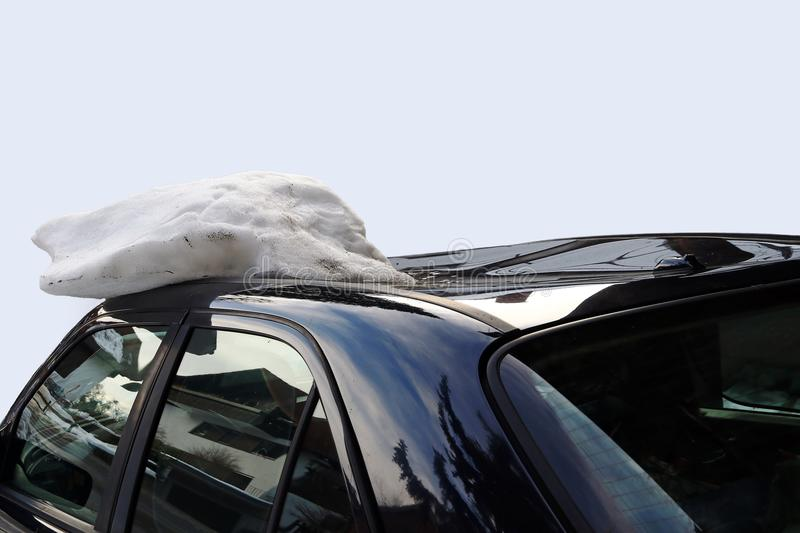 A roof avalanche damaged a black car. On the roof. Avalanche of roof damage to a car stock image