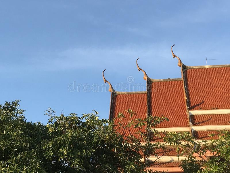 Roof of a Buddhist temple and blue sky, Nakorn Pathom, Thailand. Sacred aesthetic stock photo
