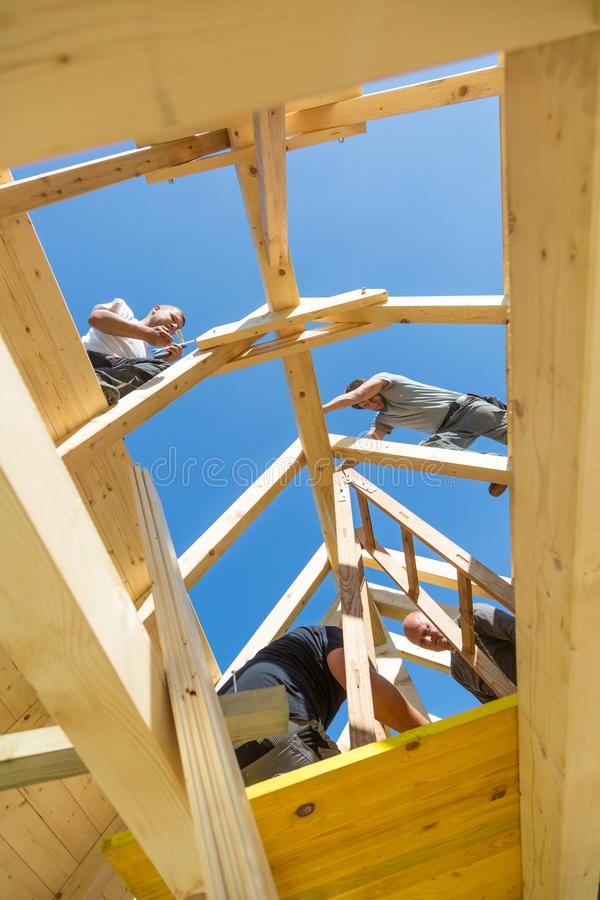 Builders at work with wooden roof construction. Roof builders mounting prefabricated wooden roof construction. Construction industry concept royalty free stock photography