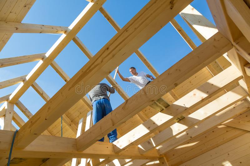 Builders at work with wooden roof construction. Roof builders mounting prefabricated wooden roof construction. Construction industry concept royalty free stock images
