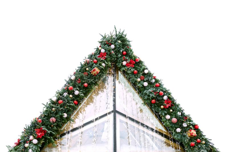 The roof of the building is decorated with spruce branches, Christmas balls, flowers and garlands. Christmas concept, decor, archi royalty free stock image