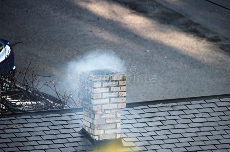 Roof with chimney coming out smoke royalty free stock image