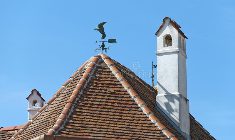 Roof with chimneys and wind vane. Red tiled roof with chimneys and the figure of a predator bird as wind vane, Koeszeg, Hungary royalty free stock image