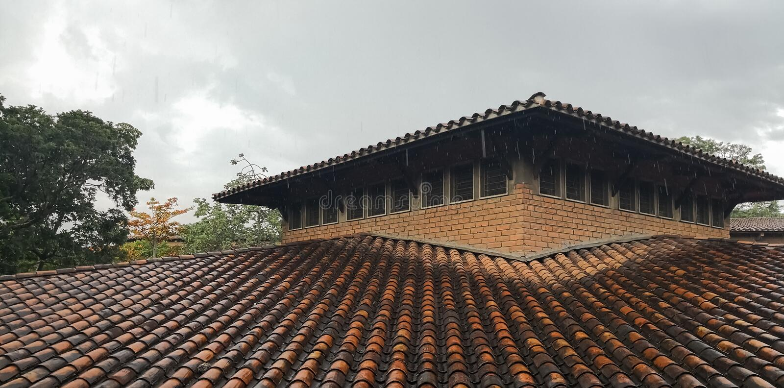 Roof with clay tiles wet from the rain. Rainy and cloudy day and detail of the brown clay tiles with contrast between those wet by the storm and those dry. Heavy royalty free stock images