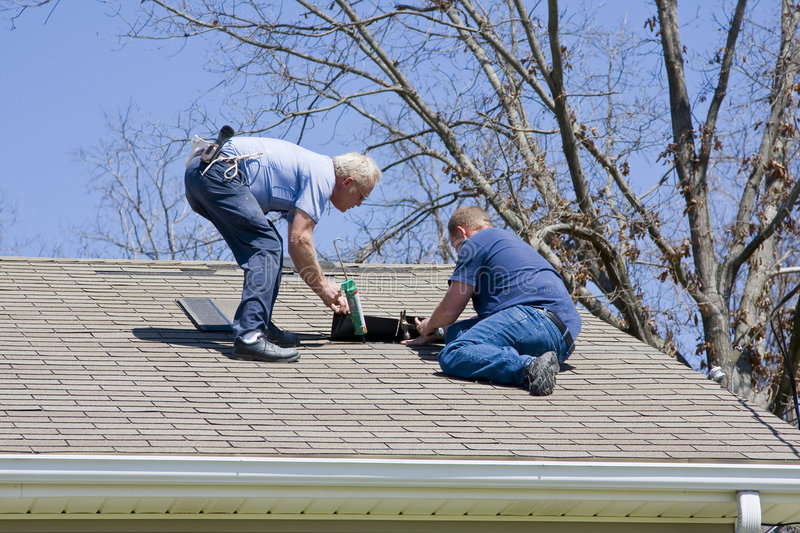 Roof Contractors. Roofing contractor repairing damaged roof on home after recent wind storms, many roofs were damaged stock images