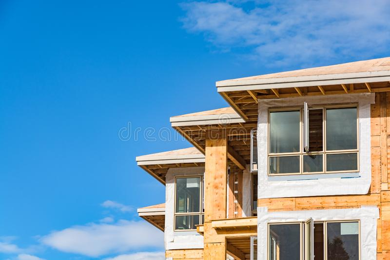 Roof corners, windows, and walls of new aparntment building under construction on the sky background royalty free stock photography