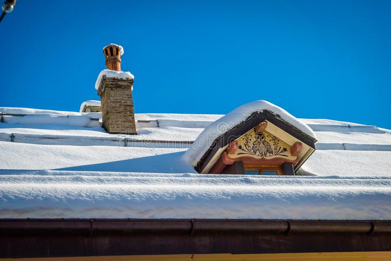 Roof covered with snow with an owl painted on the window royalty free stock photography