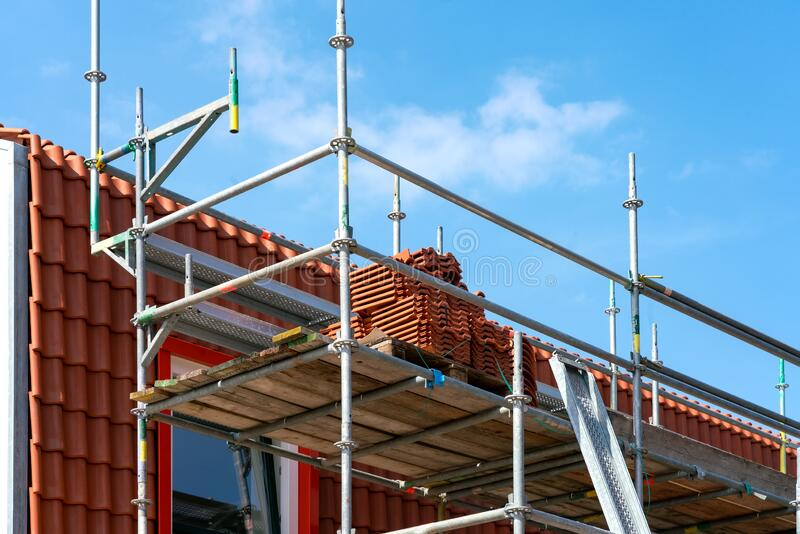 Roof covering with space for text. Roof covering. Scaffolding on a brick facade clad house. Space for text royalty free stock photo