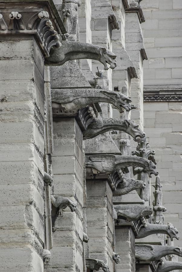 Roof figures of scary gargoyles at main facade of Notre Dame de Paris cathedral in Paris, France, closeup, details stock photography