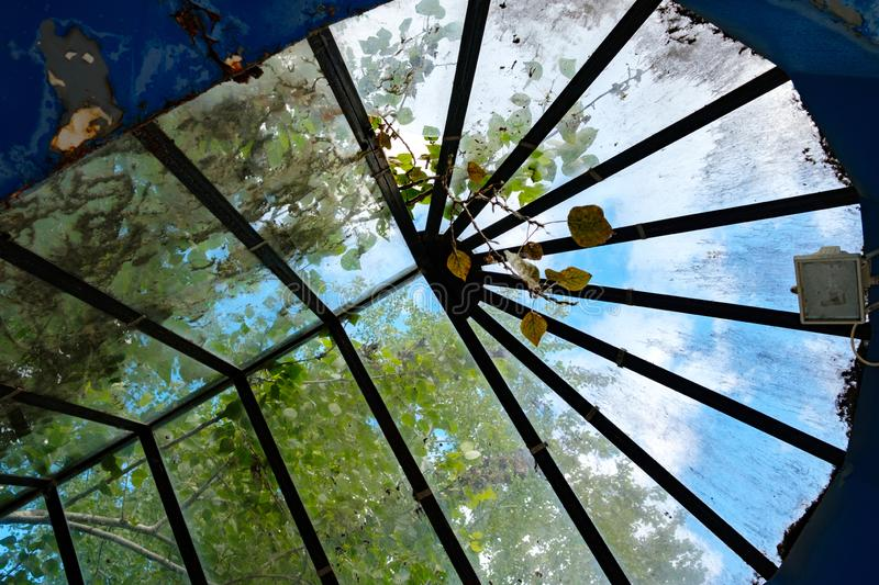 Roof in the form of glass stained glass, dirty old stained glass with leaves. And debris stock photos
