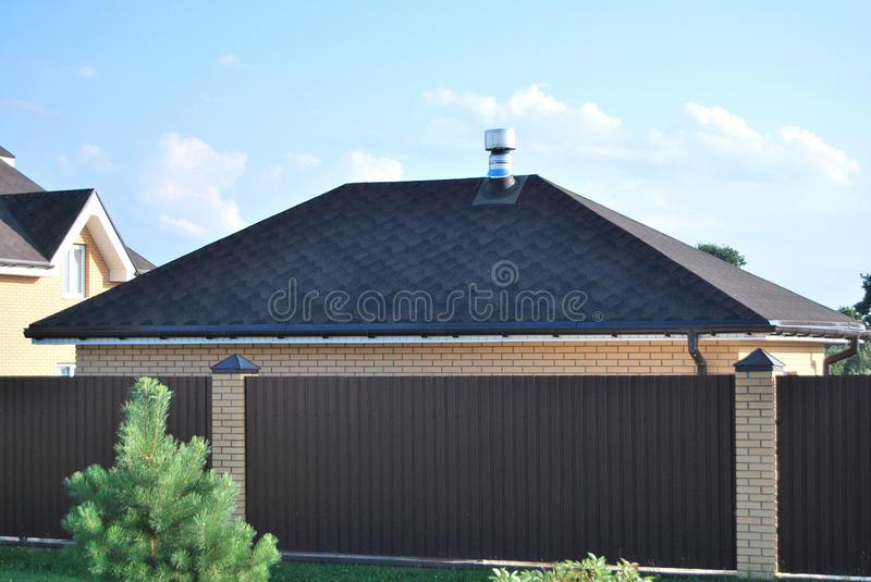 The roof of the garage. Covered with soft dark tiles, in the foreground - a brown fence stock image