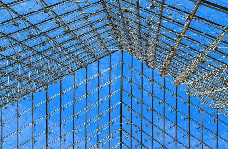 The pyramid grid roof of the Louvre in Paris, France. The roof of the glass pyramid is cold and light, It looks like a net under the blue sky stock image