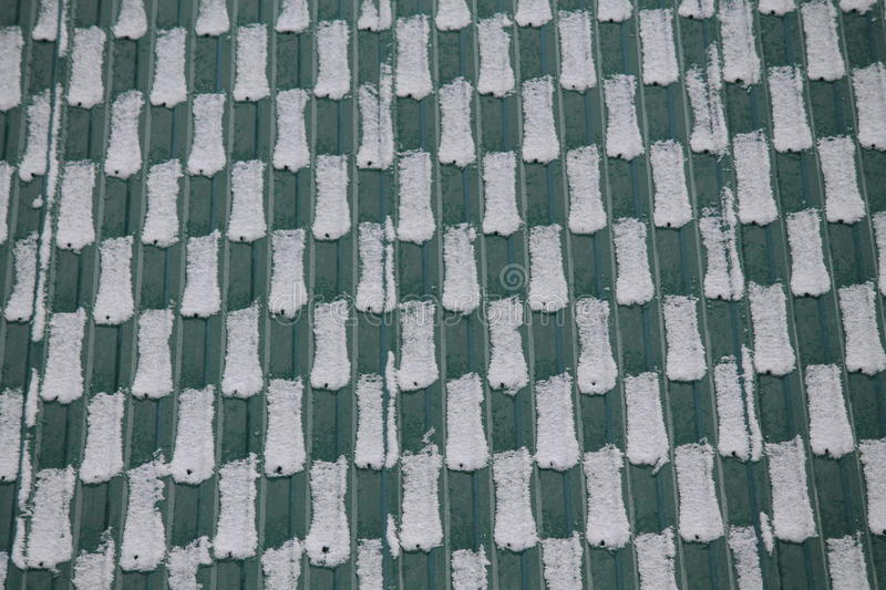Roof. Green metal roof covering white snow devision on cells stock photos