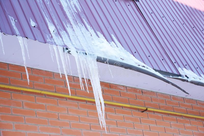 Roof Gutter damaged by ice and snow. Broken house roof gutter pipeline by icicles royalty free stock photos