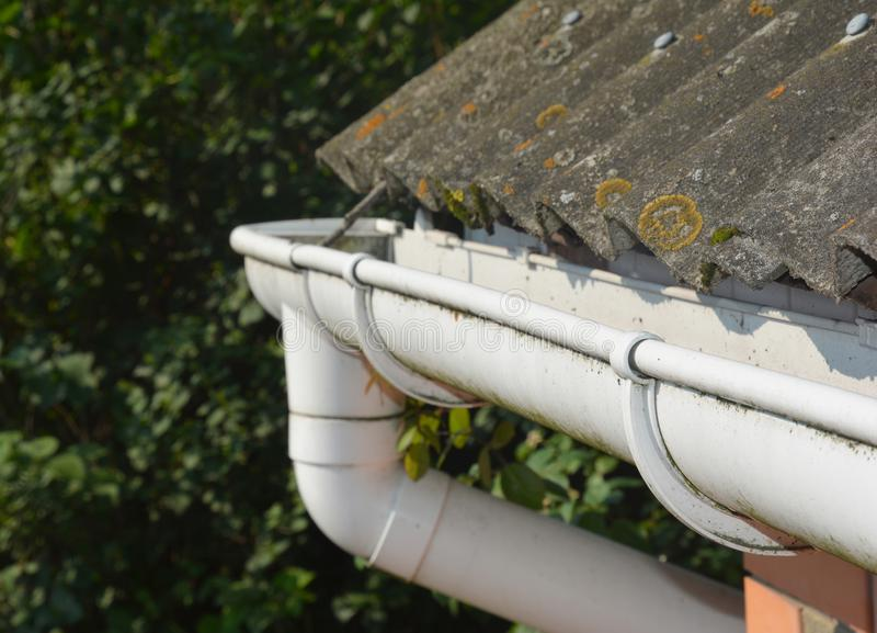 Roof gutter. House asbestos roof with plastic roof gutter pipe. House guttering with holders and old asbestos roof royalty free stock photography