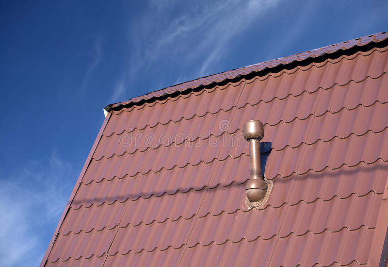Roof of a house covered with metal tile with chimney royalty free stock photos